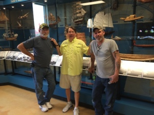 Capitol Museum Service's installation team of Bobby Boswell and Tom Mills, with Sam Heed (in the yellow jersey), just finishing the exhibit