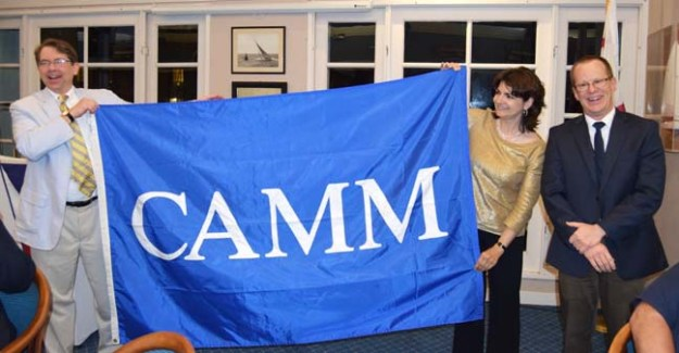 Marifrances Trivelli hands over the CAMM banner to Sam Heed of the Kalmar Nyckel Foundation as CAMM president Dave Pearson looks on. The handover of the banner from the 2015 host, Los Angeles Maritime Museum, to the 2016 host took place during the final dinner of the 2015 CAMM conference.