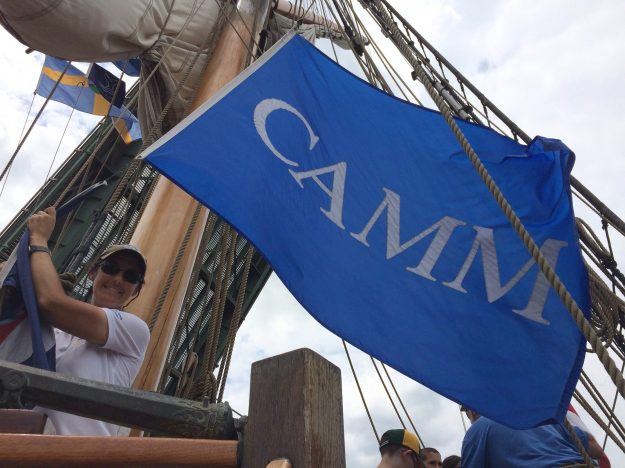 KALMAR NYCKEL captain Lauren Morgens hoists the CAMM banner. Photo from the Kalmar Nyckel Foundation Facebook page.