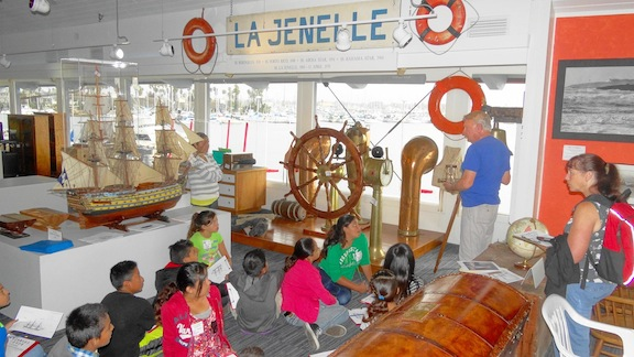 Docent Jerry Leckie talks to a group of students from Hathaway School in the Life of a Sailor Exhibit lores